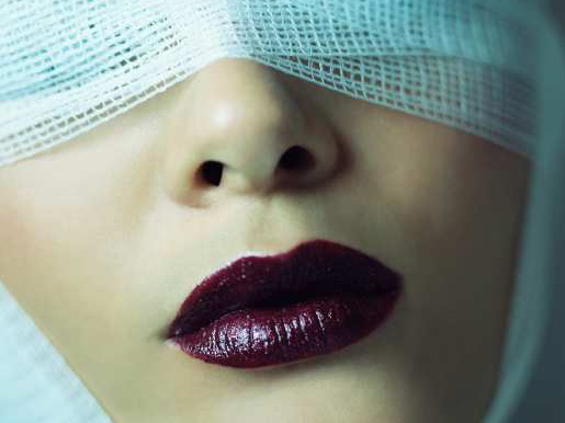 Woman wearing bandage and lipstick --- Image by © Image Source/Corbis