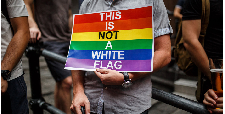 A man holds a poster depicting a rainbow flag with the message: 'This is not a white flag' as he attends a vigil in Hong Kong (Anthony Wallace/AFP)
